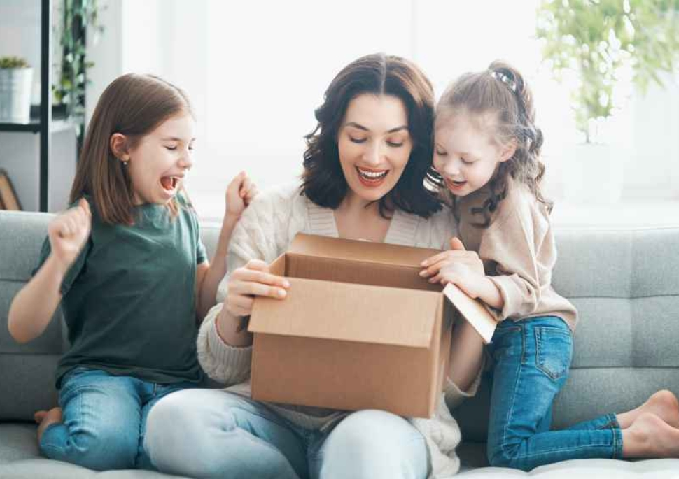 Mother and daughters are unpacking cardboard box at home.